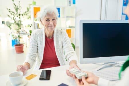 Senior lady storing money at bank
